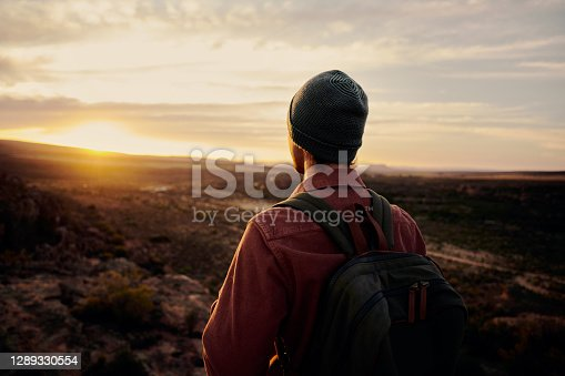 Rear view of young man standing on cliff during sunrise looking at the valley and mountains