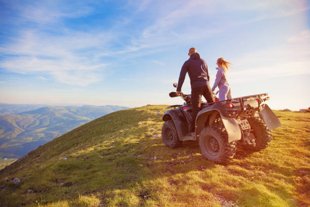 Rear view of young pair near atv. Man is showing something in distance to her girlfriend. Rear view of young pair near atv. Man is showing something in distance to her girlfriend. Blurred autumn landscape mighty mountains and forests on background quadbike stock pictures, royalty-free photos & images