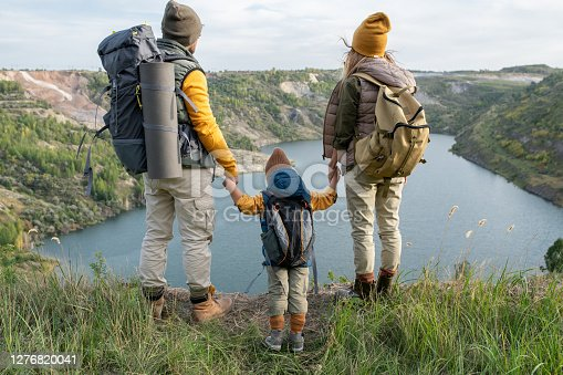 Rear view of young parents and little son with backpacks holding by hands while standing on grass and looking at lake surrounded by mountains