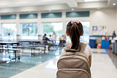 Elementary schoolgirl enters the school cafeteria. She pauses while looking for a friend.