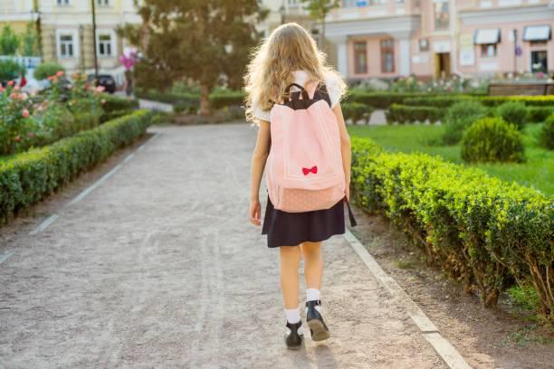 rückansicht des jungen schulmädchen in uniform mit rucksack - liebeskind umhängetasche stock-fotos und bilder