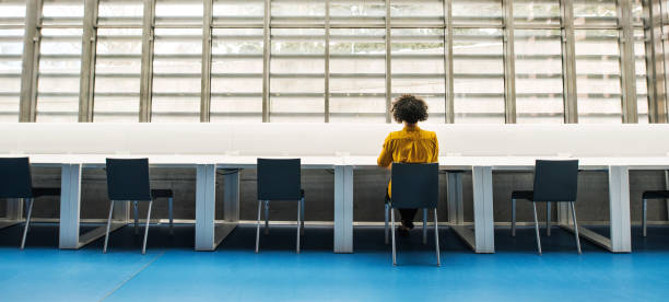 Rear view of young student or businesswoman sitting on desk in room in a library. Rear view of young student or businesswoman sitting on desk in room in a library or office. empty desk stock pictures, royalty-free photos & images