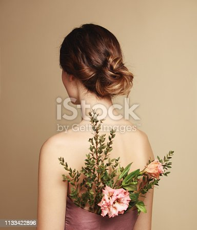 Portrait of woman with flowers behind her back