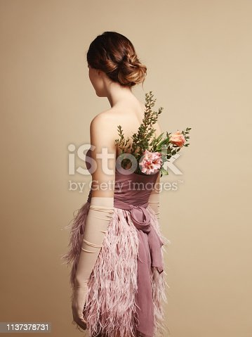 Rear view of young woman wearing pink dress with feathers and flowers