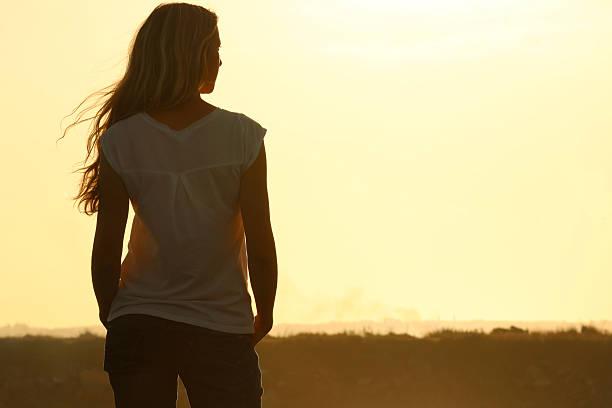 vista posterior de joven mujer en la puesta de sol - chica rubia espaldas fotografías e imágenes de stock