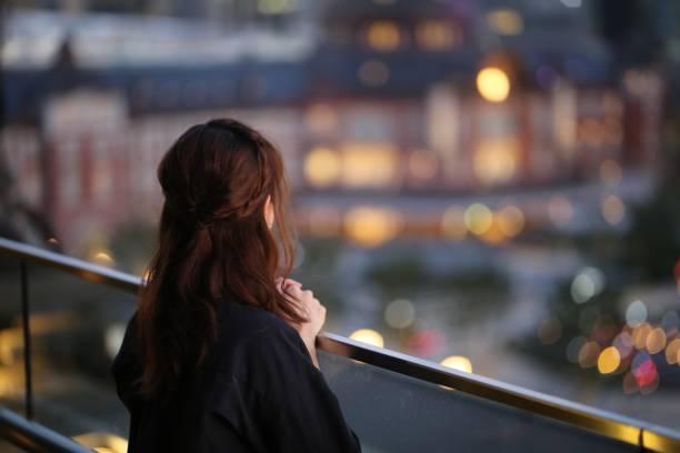 陽臺上的年輕女子後視圖圖像檔