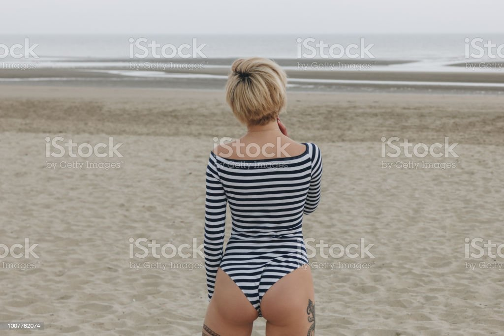 rear view of young woman in striped bodysuit on sandy seashore