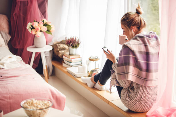 Rear view of young woman relaxing next to her window and enjoying coffee while using her smart phone stock photo
