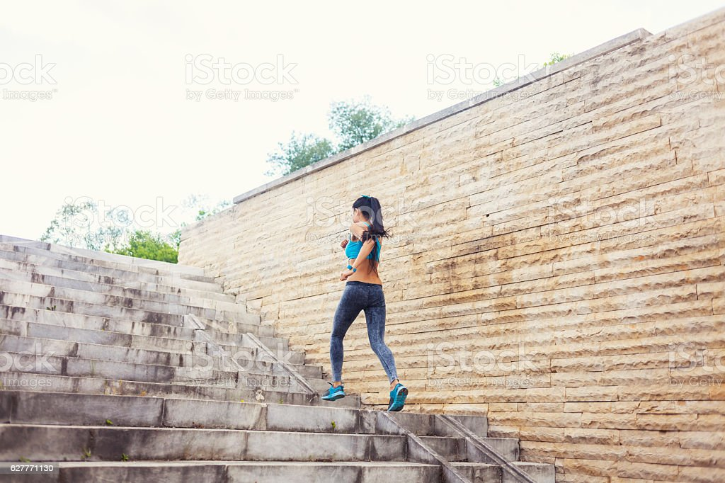 Rear view of young woman running up on stairs stock photo