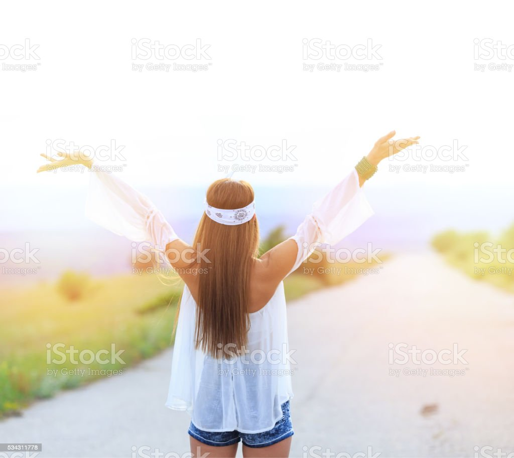 Rear view of young woman standing on the road stock photo