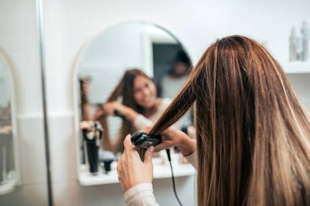 achteraanzicht van jonge vrouw straighten van haar met straightener. - bijstellen stockfoto's en -beelden