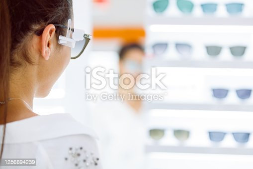 Rear view of young woman wearing sunglasses to try them on in eyewear shop