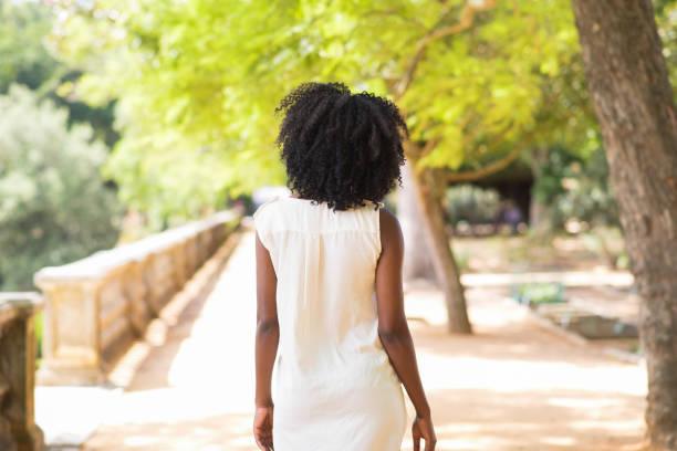 genç kadının park'ta yürüyordunuz arkadan görünüş - beyaz elbise stok fotoğraflar ve resimler