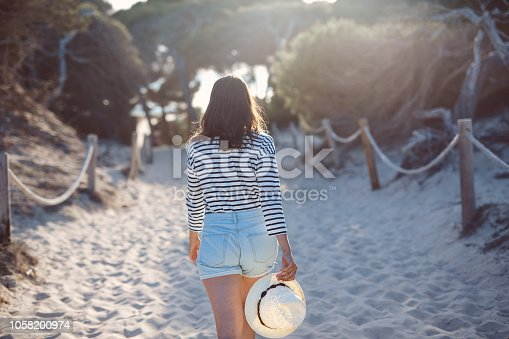 A photo of young woman walking on sandy footpath amidst plants in the summer. She is holding her hat in a hand, backlit by setting sun.