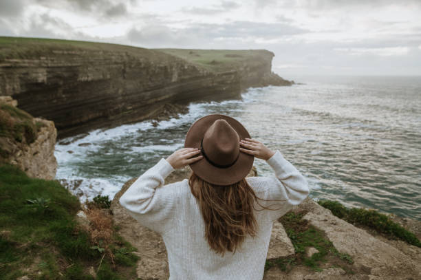 Rear view of young woman with hat by cliffs at sunset stock photo