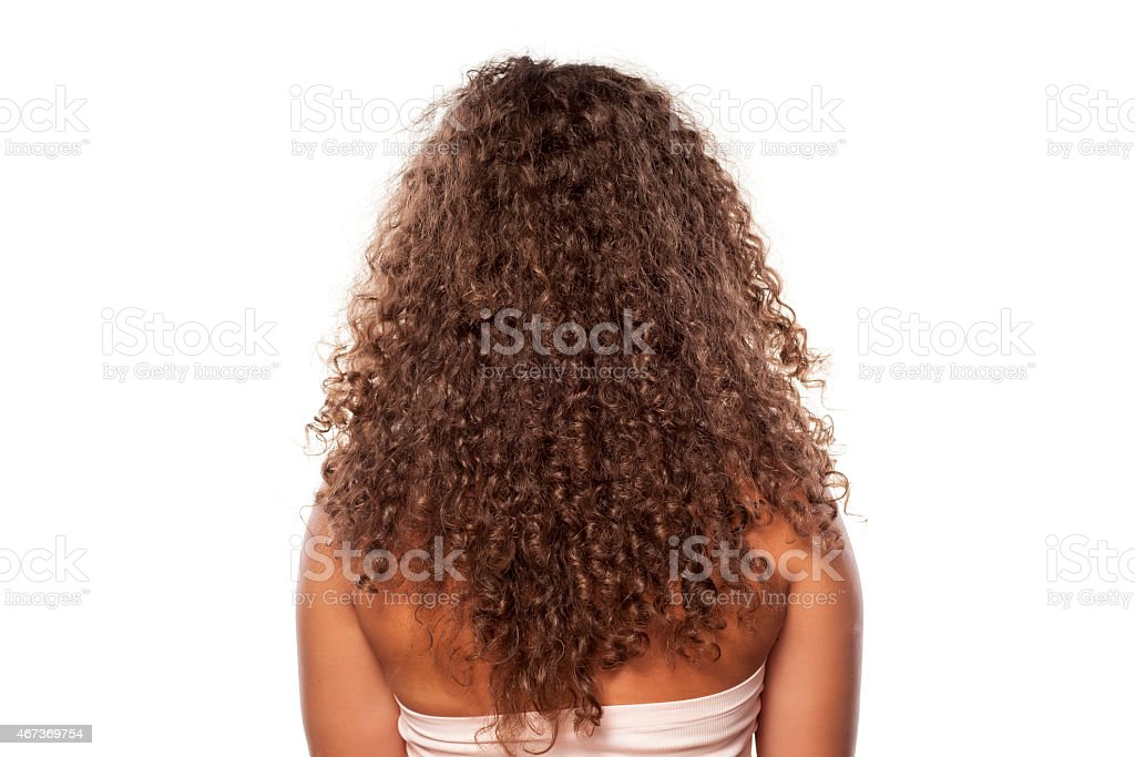 Rear view of young woman with long curly hair stock photo