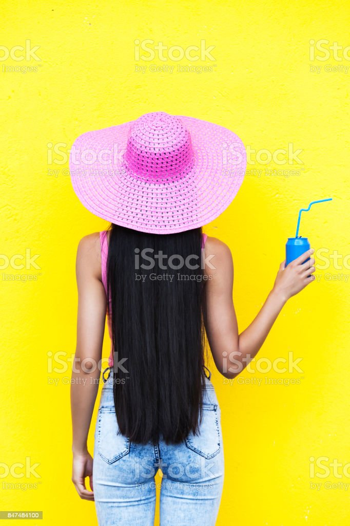 Rear view of woman with pink beach hat holding blue can in front of...