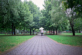 Rear view of young womanl under a bright umbrella, walking in rain