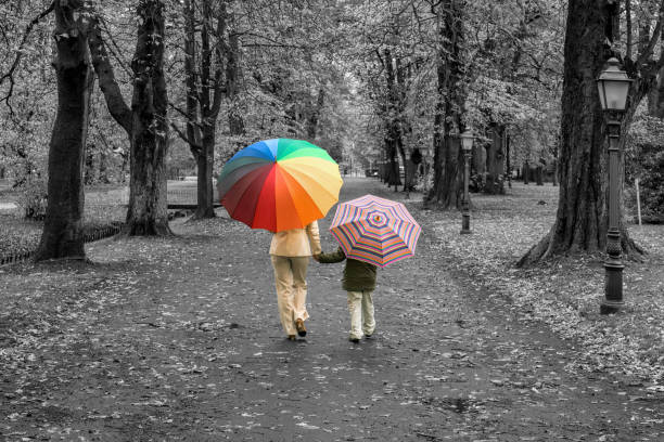 Rear view on mother and son with umbrellas in isolated color walking hand in hand in black and white park stock photo
