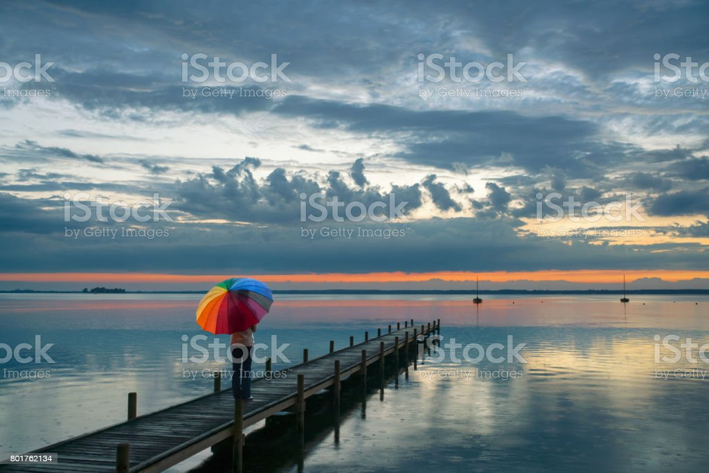 Rear view on woman with multi colored umbrella in rain on lakeside jetty watching reflection of majestic cloudscape at dusk stock photo