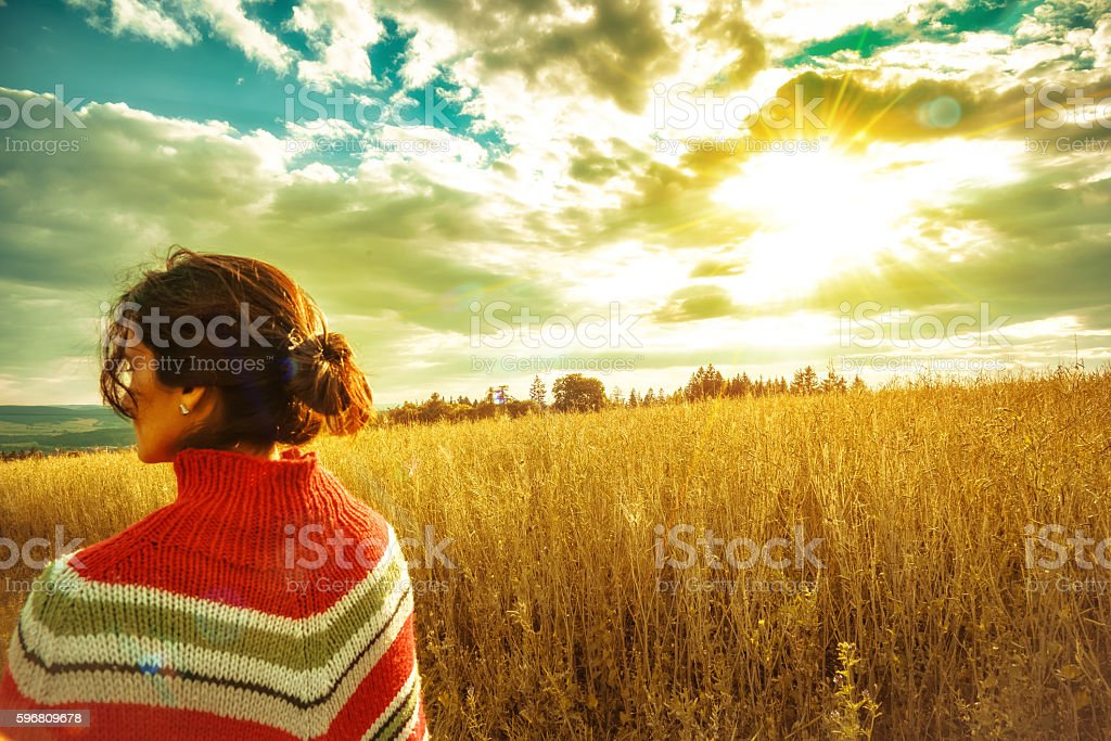 rear view on woman with poncho standing in summer field stock photo