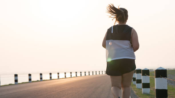 Rear view Overweight Asian women jogging in the street in the early morning sunlight. concept of losing weight with exercise. with copy space. stock photo