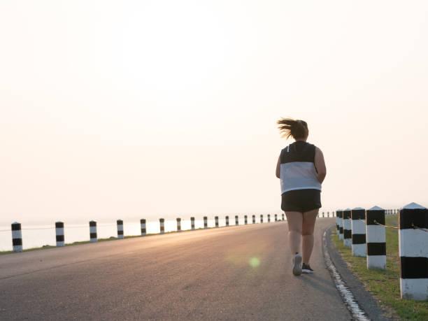 Vista posterior con sobrepeso mujeres asiáticas que trotar en la calle en la luz del sol temprano por la mañana. concepto de perder peso con el ejercicio. con el espacio de copia. - foto de stock