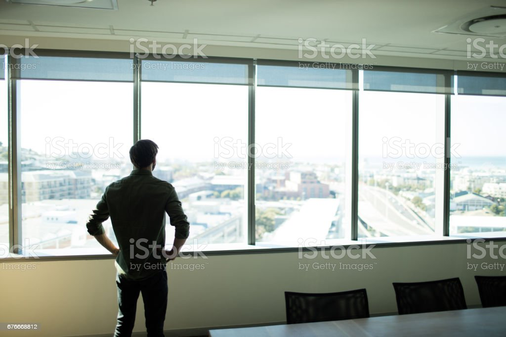 Rear view pf businessman looking through window at workplace stock photo