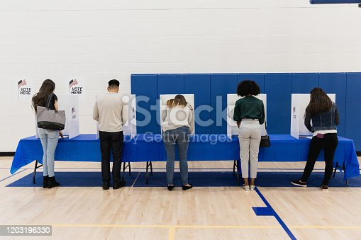 A rear view of a multi-ethnic group of people casting their ballots in the election.