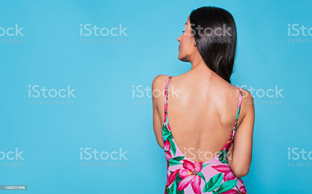 Rear view photo of cute brunette woman  in summer dress posing on blue background stock photo