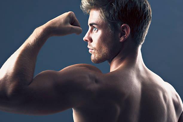 Vista traseira Retrato de homem Flexionando Músculos de bíceps - foto de acervo