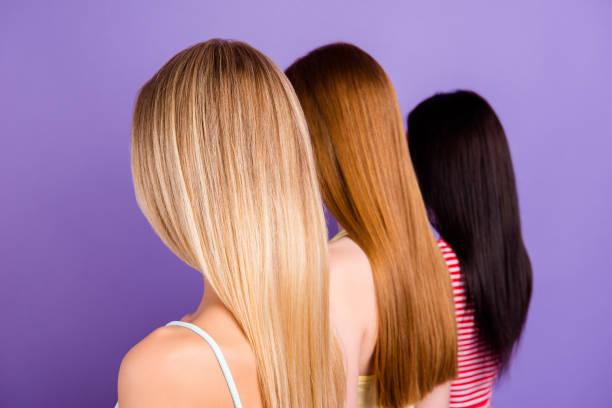 hintere ansicht porträt trio mit anderen haarfarbe nach haarschnitt im beauty-salon auf lebendige violettem hintergrund isoliert. haar behandlung therapiekonzept - haarfarbe ohne ammoniak stock-fotos und bilder