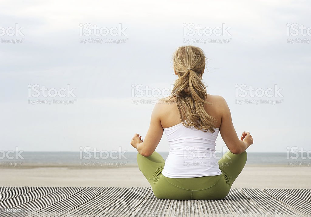 Rear view portrait of young woman sitting at beach yoga royalty-free stock photo
