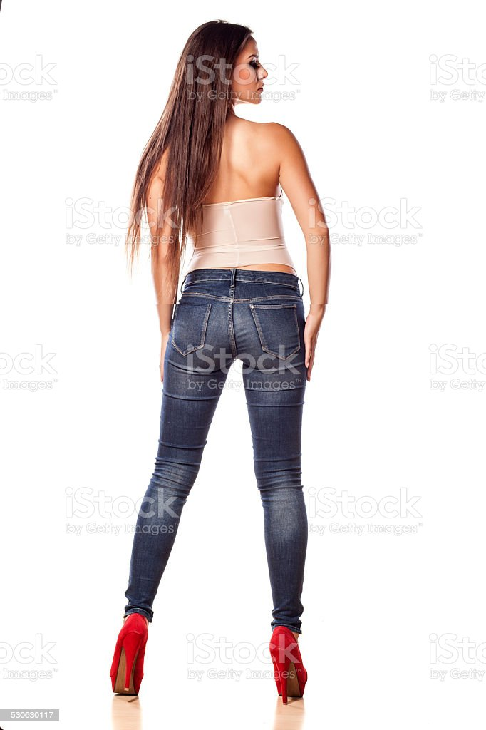Rear view pretty girl in jeans posing on  white background stock photo