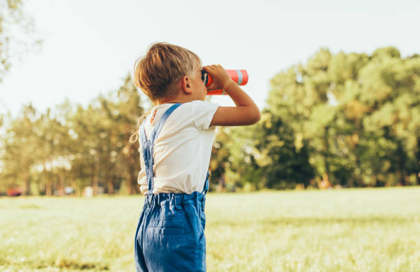 Rear view shot of little boy looking through a binoculars searching for an imagination or exploration in summer day in park. Happy child playing pretend safari game outdoors in the forest. Childhood stock photo