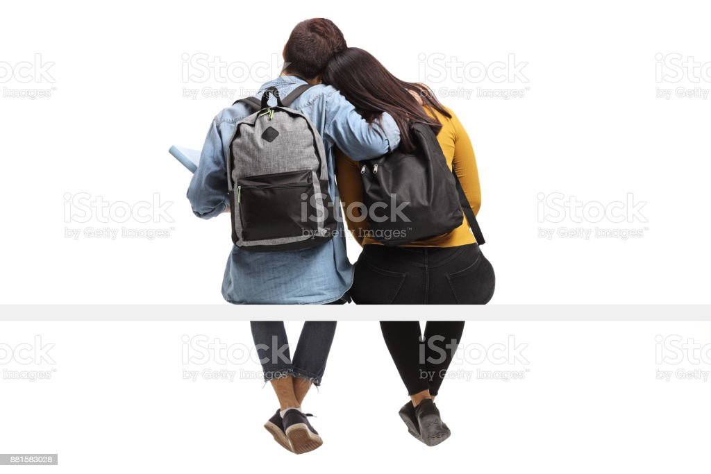 Rear view shot of teen students seated together in an embrace stock photo