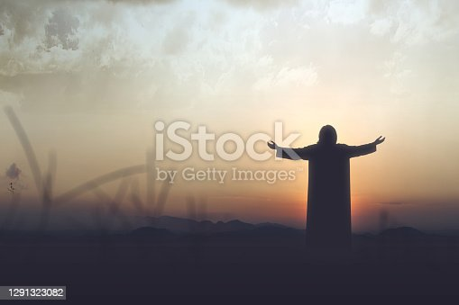 Rear view silhouette of Jesus Christ raised hands and praying to god with a sunset sky background