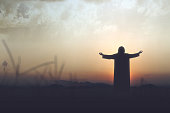 istock Rear view silhouette of Jesus Christ raised hands and praying to god 1291323082