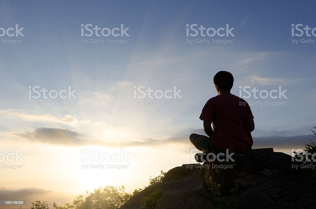 Rear view silhouette of man sitting atop peak at sunset royalty-free stock photo