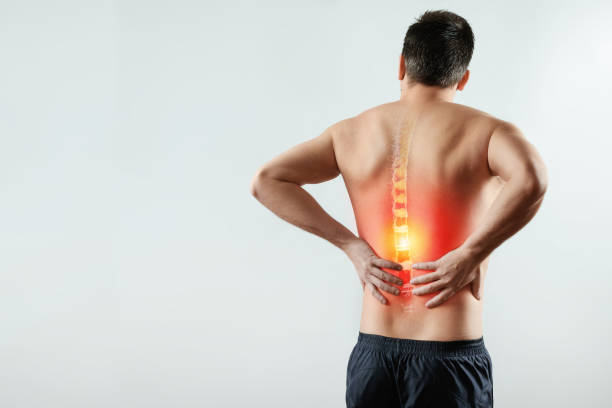 Rear view, the man holds his hands behind his back, pain in the back, pain in the spine, highlighted in red. Rear view, the man holds his hands behind his back, pain in the back, pain in the spine, highlighted in red. Light background. The concept of medicine, massage, physiotherapy, health. back pain stock pictures, royalty-free photos & images