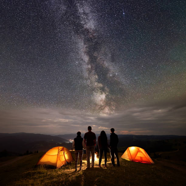 rear view two young couples at night in tent camp stand enjoying starry sky, milky way, mountains and luminous town - falò foto e immagini stock