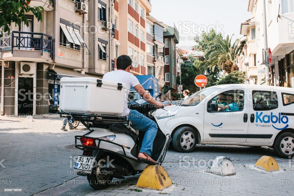 Rear view - unidentified driver sitting behind the wheel of small moped with white box - luggage stock photo