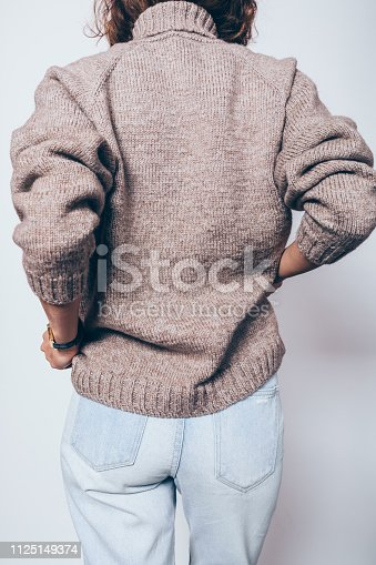 Rear view unrecognizable young woman wearing knitted brown oversized sweater and blue jeans standing over white background. Details of trendy casual clothing for winter.