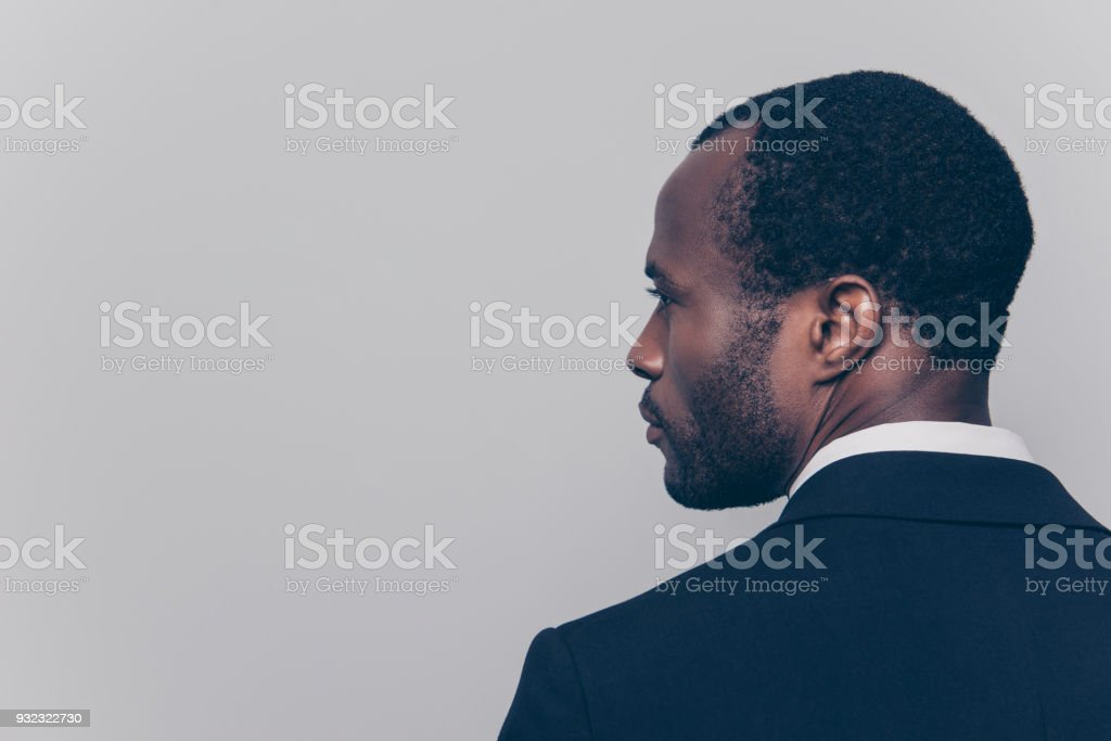 Rear view with half turned head, close up portrait with copy space, empty place for advertisement of confident, attractive, concentrated manager, guy in tux, isolated on grey background stock photo