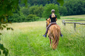 back view of woman riding her chestnut colored horse through high grass