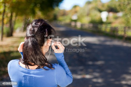 istock rear view woman with earbuds - horizontal 2 453883339