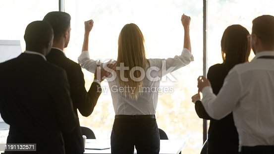 1141929391 istock photo Rear view young female professional celebrating company success. 1191132571