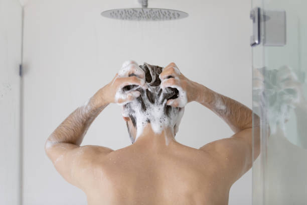 Rear view young man washing hair, standing in bathroom stock photo