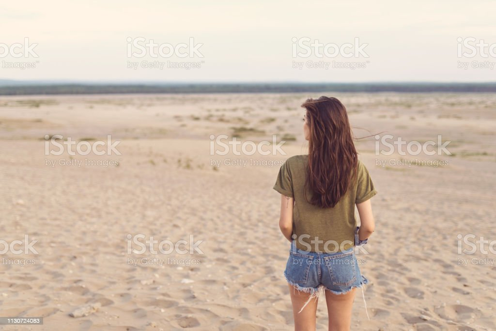 Rear view young woman lost in desert Rear view young woman lost in desert. Female with brown hair is standing on sand. Hiker is visiting arid landscape during summer vacation. 25-29 Years Stock Photo