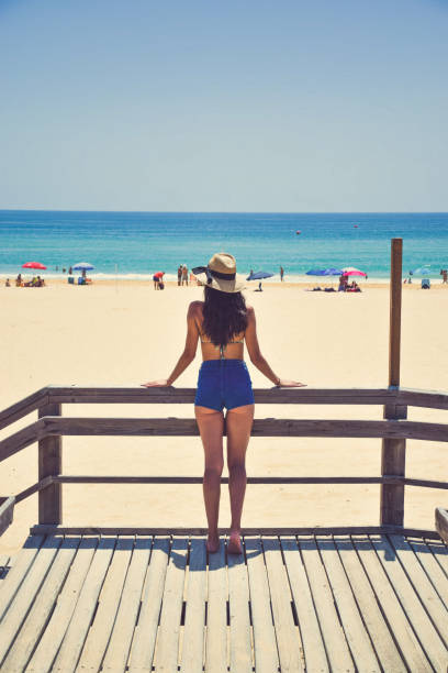 Rear View Young Woman Standing Enjoying Beach Day Rear View Young Woman Standing Enjoying Beach Day middle aged women in bikinis stock pictures, royalty-free photos & images
